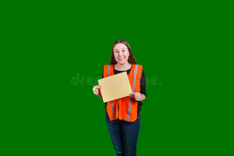 Female wearing orange reflecting safety vest holding blank yellow sign. Young female wearing orange reflecting safety vest holding blank yellow whiteboard in stock photo