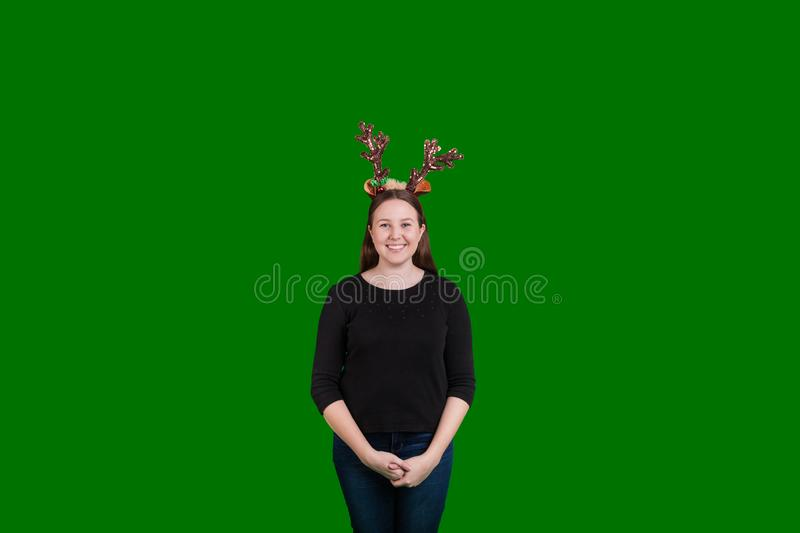 Female wearing Christmas reindeer antlers smiling captured on green screen background. Young blond female wearing holiday Christmas reindeer antlers smiling stock images