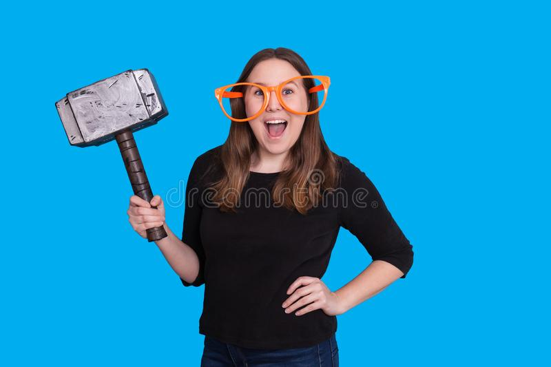 Young lady holding a rubber mallet hammer photo prop and big orange glasses photo booth portrait. Young lady excited expression on her face holding a rubber royalty free stock photo