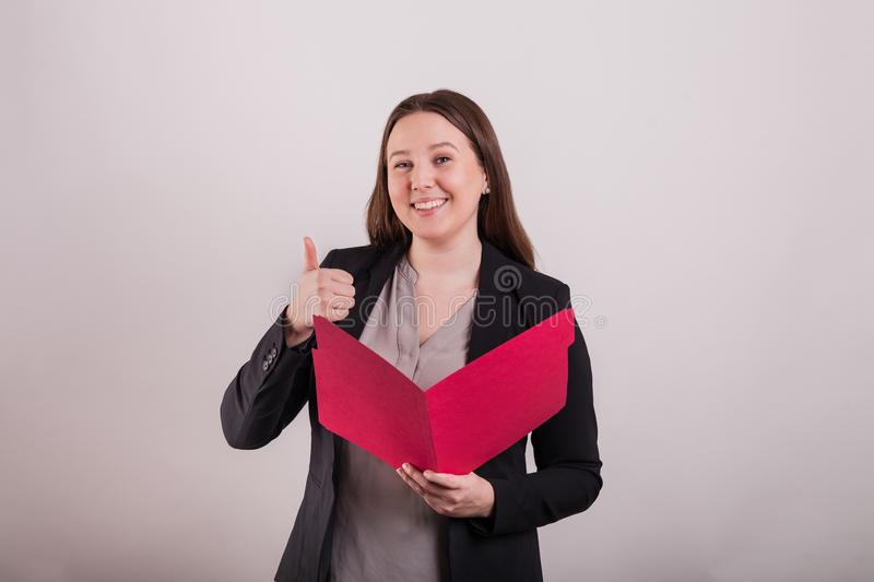 Professional female gesturing a thumbs up holding a red file folder. Professional young female wearing a business suit gesturing a thumbs up holding a red file royalty free stock photo