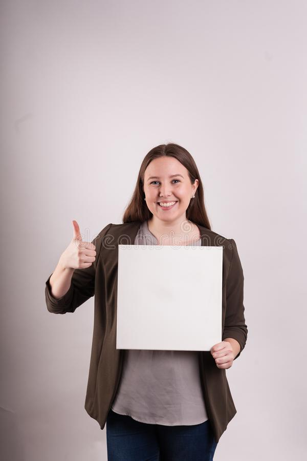 Young professional business women gesturing a thumbs up holding a white poster royalty free stock photography