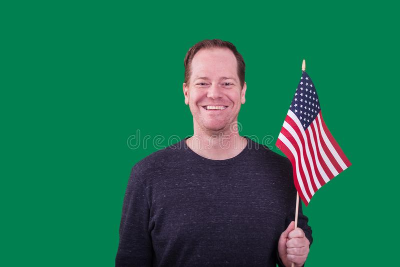 Portrait of patriotic adult man holding a American flag smiling on green screen backdrop royalty free stock images