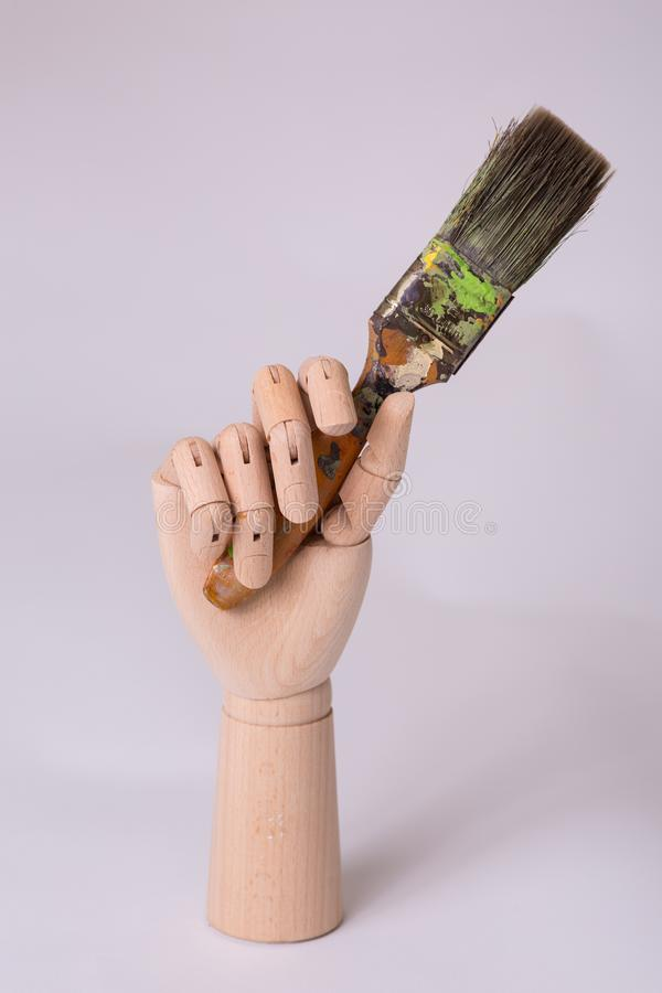 Wooden jointed manikin hand holding up a painters art brush studio shot stock image