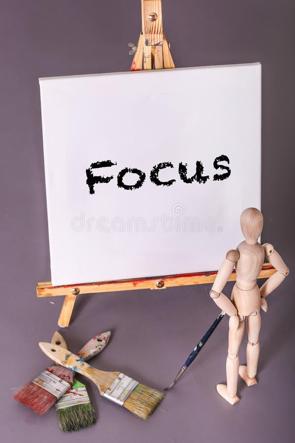 Message board with Focus painted on it wooden manikin standing with hands on hip royalty free stock photo