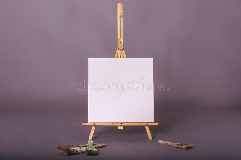 Blank white canvas sitting on artist easel paint brushes scattered stock photo