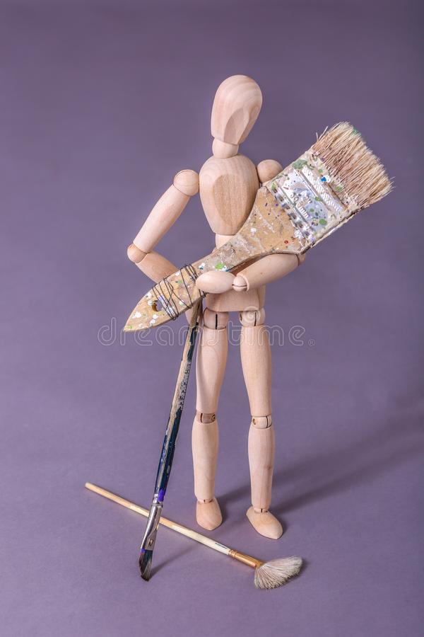 Wooden manikin doll standing holding large paintbrush stock photo