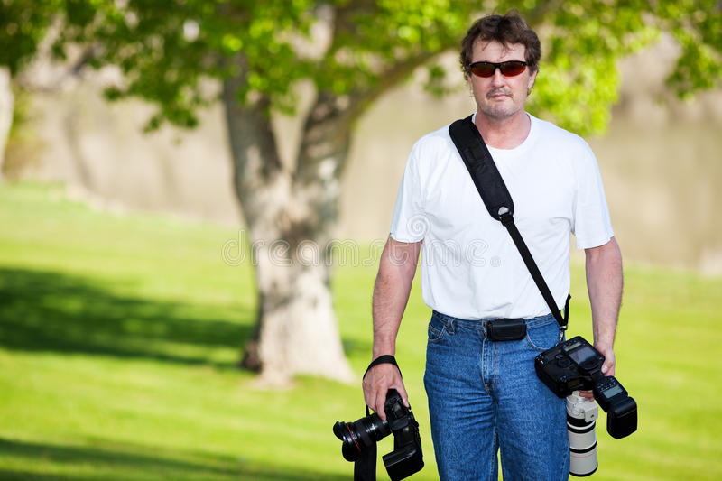 Professional Photographer. A professional photographer armed with two cameras, walking on the grassy shores of a river stock photo