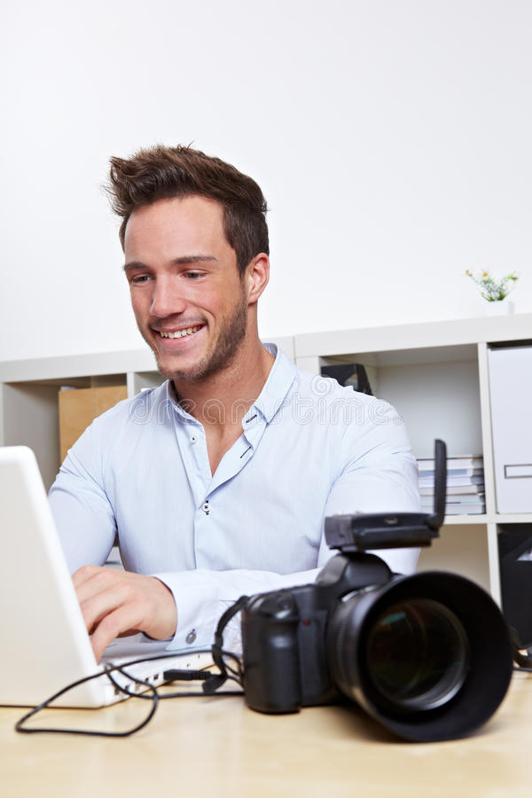 Professional photographer. With camera and laptop computer in office royalty free stock photos