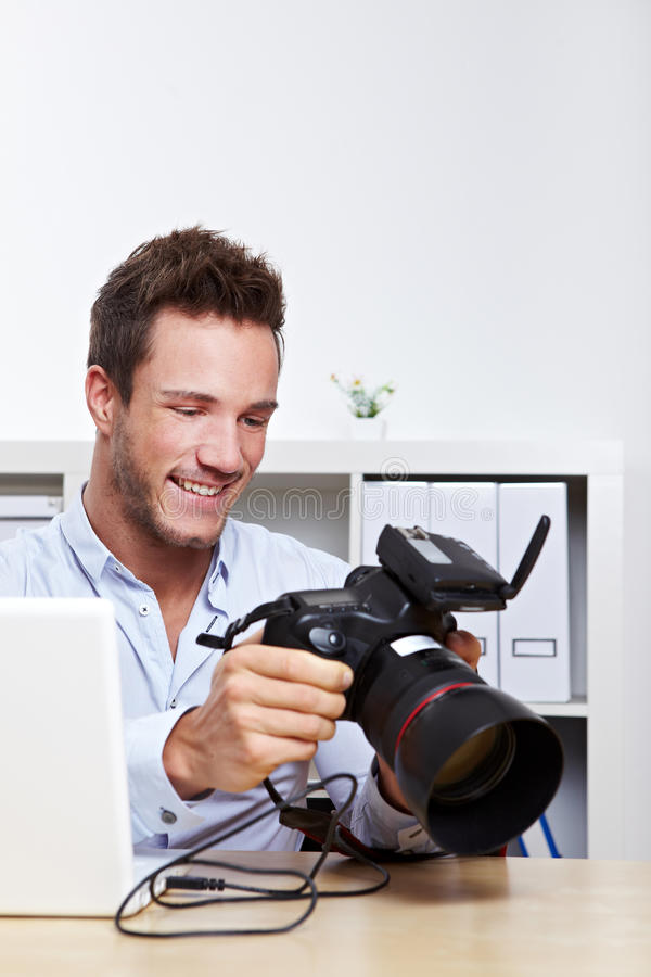 Professional photographer. With camera in office making image backup royalty free stock photo