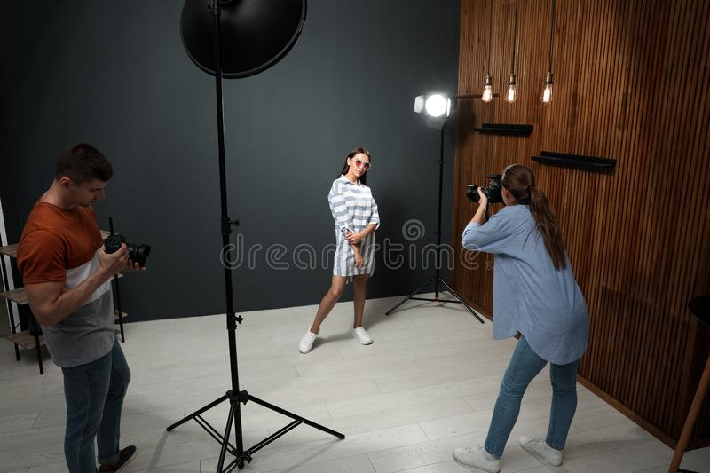 Professional photographer with assistant taking picture of young man in studio. Professional photographer with assistant taking picture of young men in modern stock photography