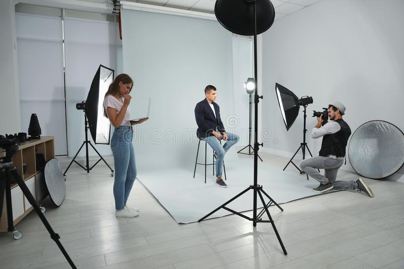 Professional photographer with assistant taking picture of young man in studio. Professional photographer with assistant taking picture of young man in modern stock photography