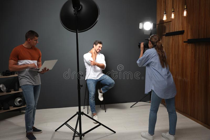 Professional photographer with  taking picture of young man in modern studio. Professional photographer with assistant taking picture of young men in modern royalty free stock image