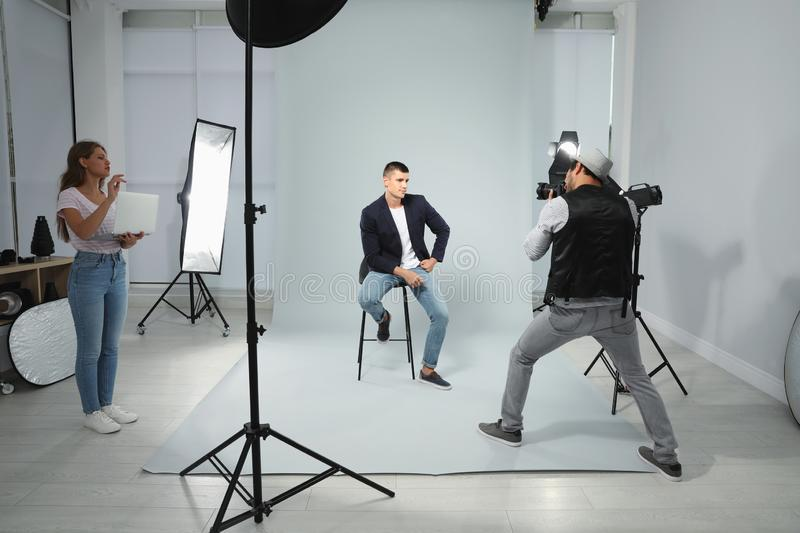 Professional photographer with  taking picture of young man in modern studio. Professional photographer with assistant taking picture of young men in modern royalty free stock photo