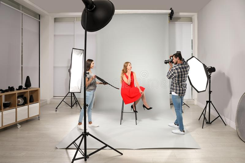 Professional photographer with  taking picture of young woman in modern studio royalty free stock image
