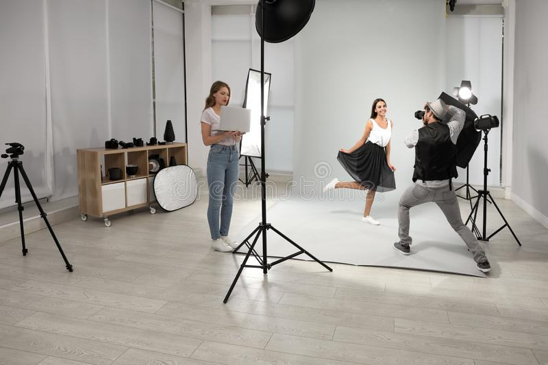 Professional photographer with  taking picture of young woman in modern studio. Professional photographer with assistant taking picture of young women in modern royalty free stock images