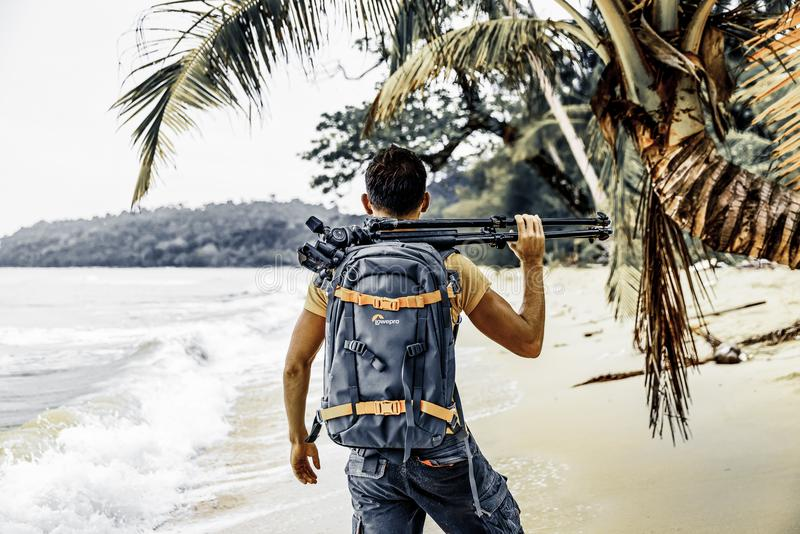 Professional photographer with camera and tripod on nature background. Bali / Indonesia - JUN18 2018: Professional travel photographer explore tropical beach royalty free stock photo