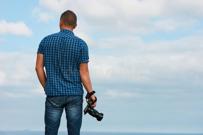 Professional photographer with digital camera. In his hand over blue cloudy sky and sea background, back view, copy space stock photos