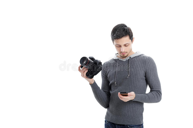 Professional photographer with DSLR digital camera looking phone. Young successful professional photographer in shirt with DSLR digital camera looking phone royalty free stock photos