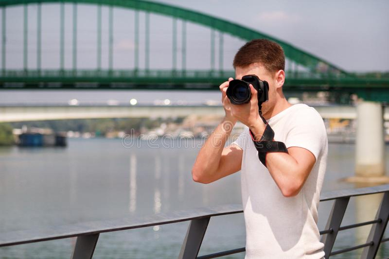 Photographer examining scenery and taking pictures of environment, architecture, urban elements, river, old green bridge. stock photo
