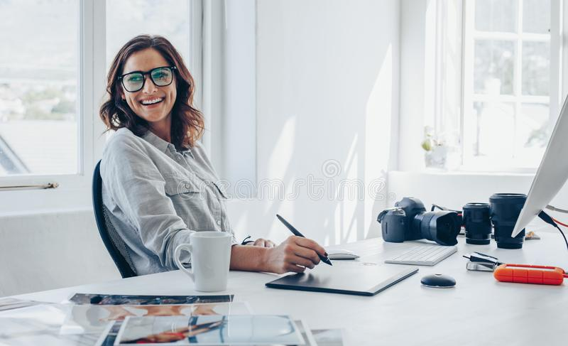 Professional photographer at her office desk. Professional photographer sitting at her office desk looking away and smiling. Woman in office with digital graphic royalty free stock images