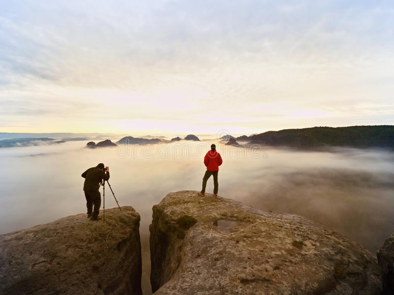 Professional photographer and hiker shooting in wild nature with a digital camera and a tripod. View over clouds to morning horizon stock photo