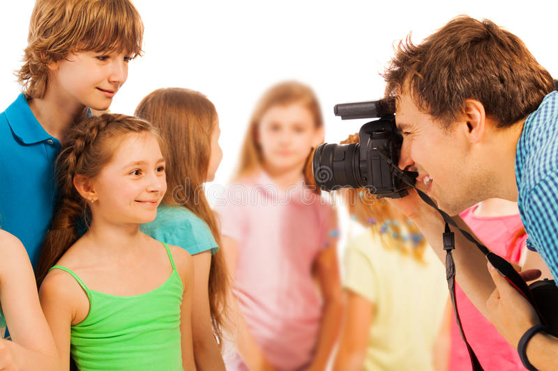 Professional photographer photographing kids. Adult photographer photographing beautiful kids boys and girls with dslr camera stock images