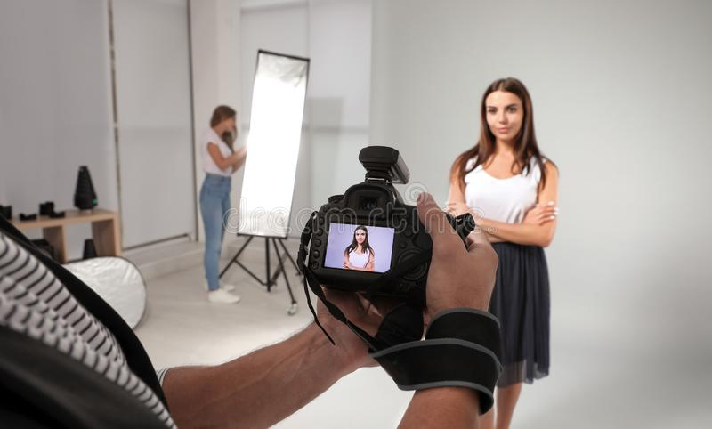Professional photographer  picture on camera and model with assistant in studio. Professional photographer reviewing picture on camera and model with assistant stock image