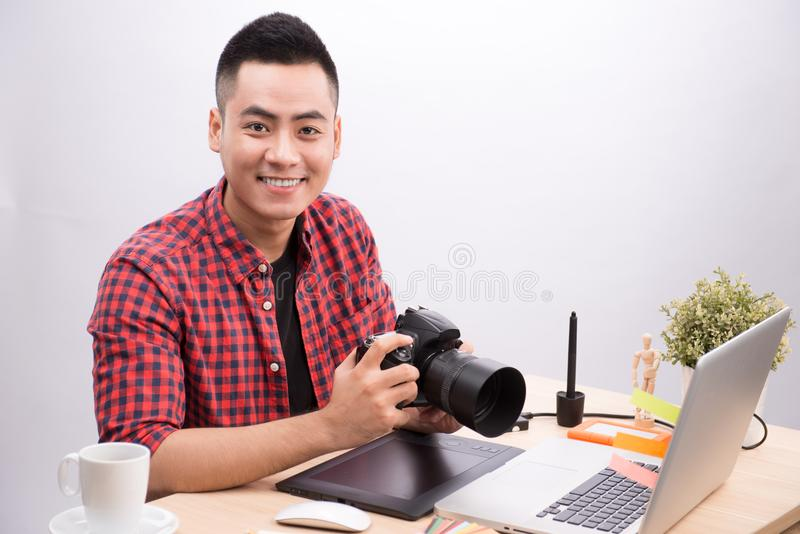 Professional photographer. Portrait of confident young man in sh. Irt holding hand on camera while sitting at his desk stock photo