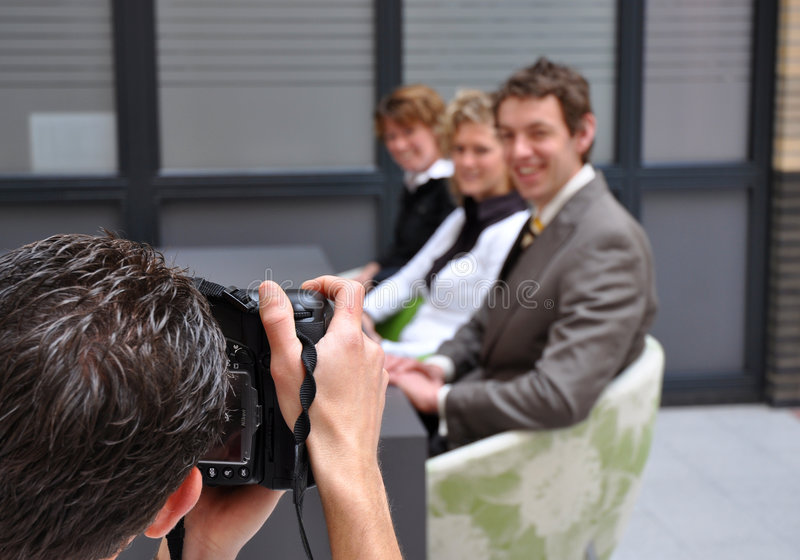 Professional photographer shooting business people. Professional photographer shooting business models royalty free stock photography