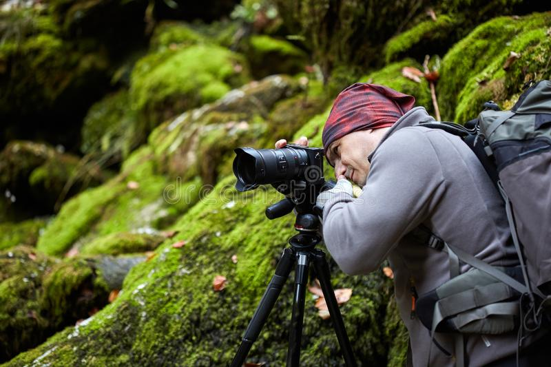 Professional nature photographer. Professional photographer shooting with camera on tripod in a canyon royalty free stock photography