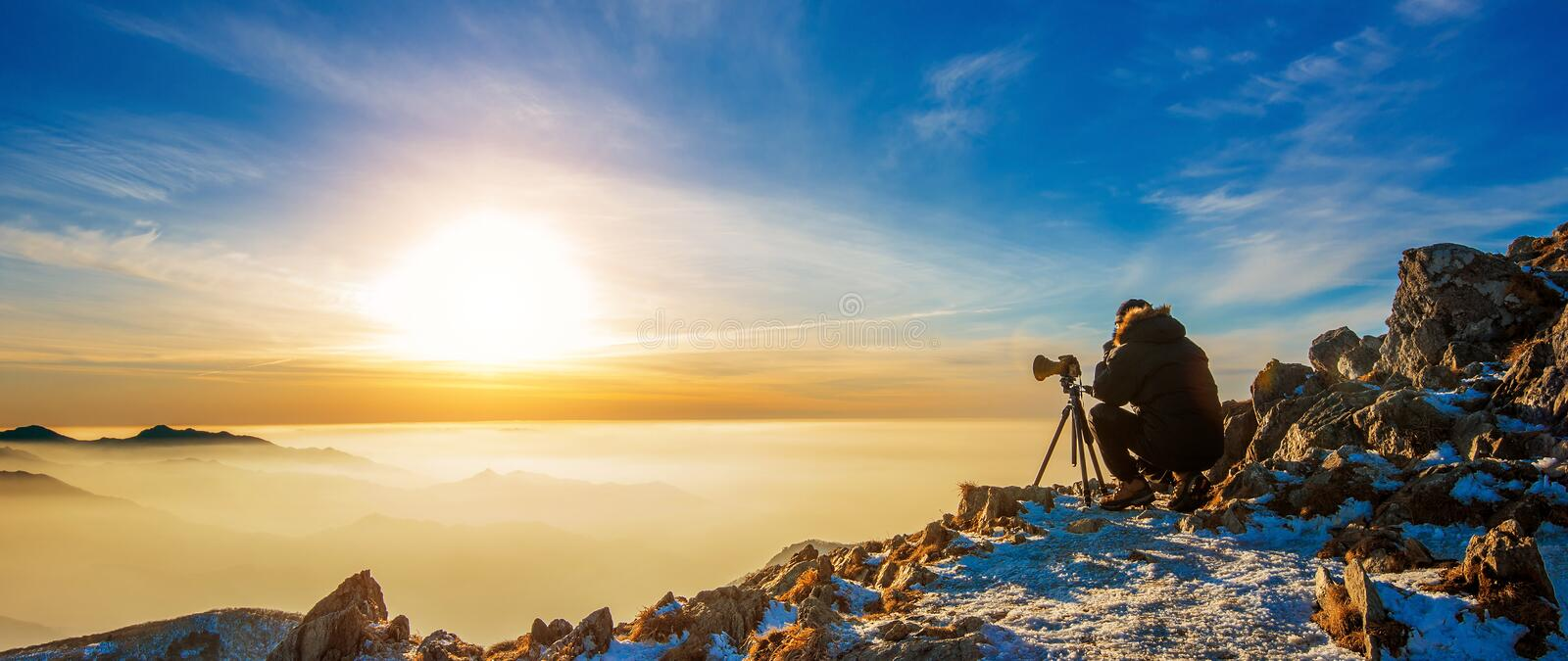 Professional photographer takes photos with camera on tripod on. Rocky peak at sunset stock photography