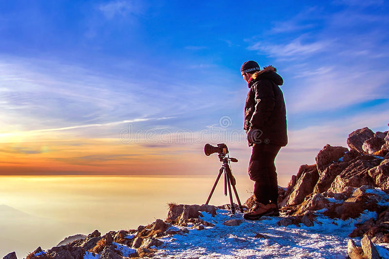 Professional photographer takes photos with camera. stock image