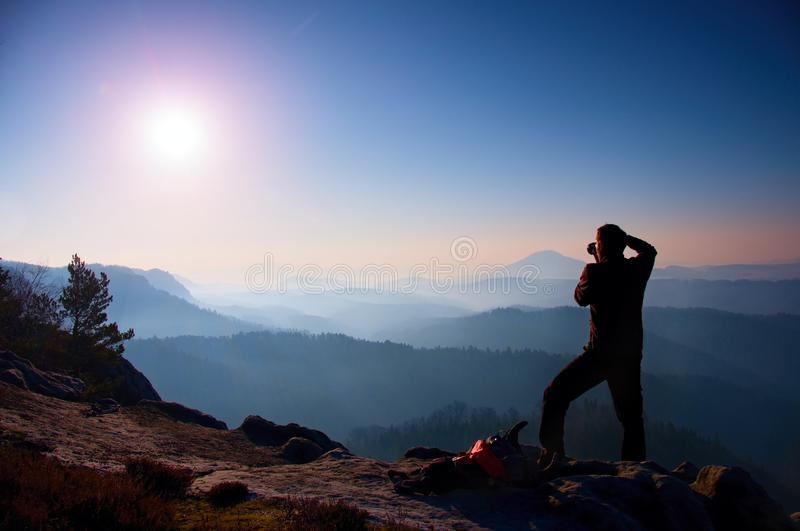 Professional photographer takes photos with mirror camera on peak of rock. Dreamy fogy landscape, spring orange pink misty sunrise. In a beautiful valley below royalty free stock image