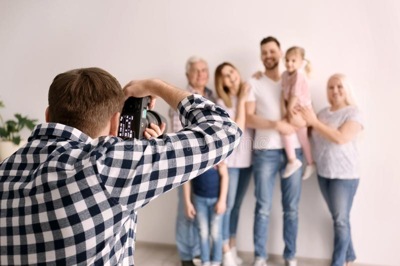 Professional photographer taking photo of family. In studio royalty free stock image
