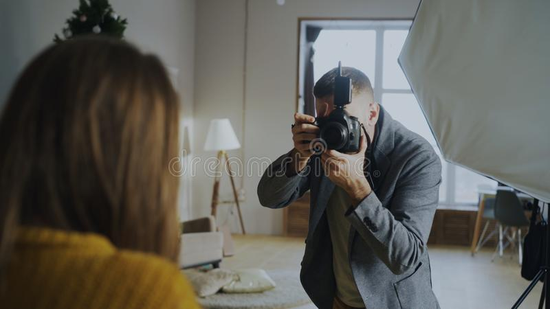Professional photographer taking photos of model on digital camera working in photo studio. Indoors royalty free stock image