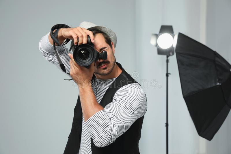 Professional photographer taking picture in studio. Professional photographer taking picture in modern studio royalty free stock photos