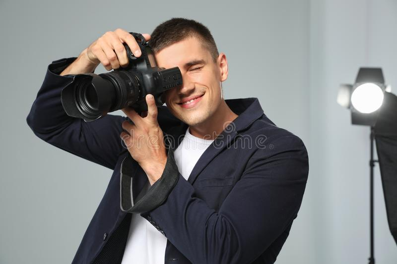 Professional photographer taking picture in studio. Professional photographer taking picture in modern studio stock image