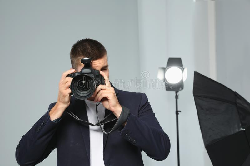 Professional photographer taking picture in studio. Professional photographer taking picture in modern studio royalty free stock images