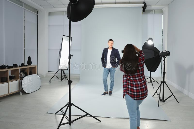 Professional photographer taking picture of young man in studio. Professional photographer taking picture of young men in modern studio royalty free stock photography