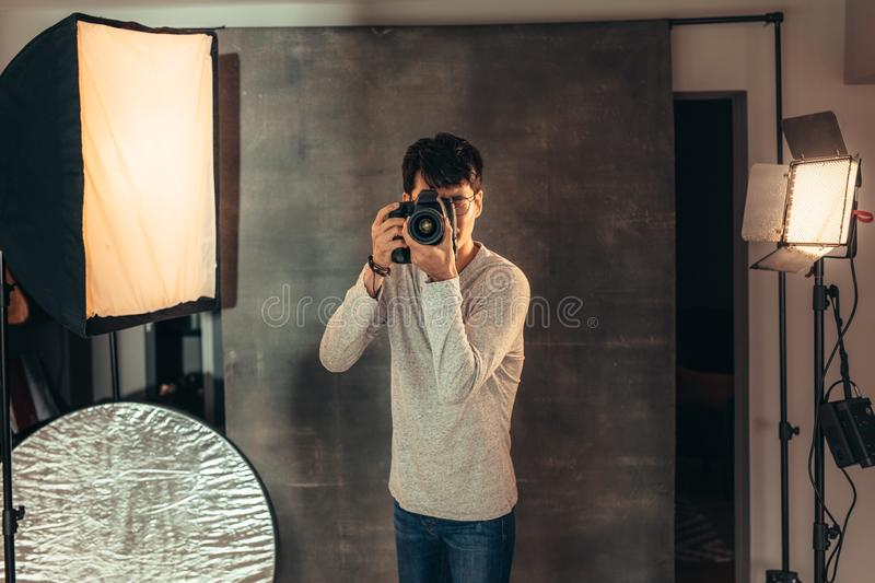 Professional photographer taking pictures in studio. Photographer standing in studio to take a photograph with flash lights on his side. Professional male royalty free stock photos