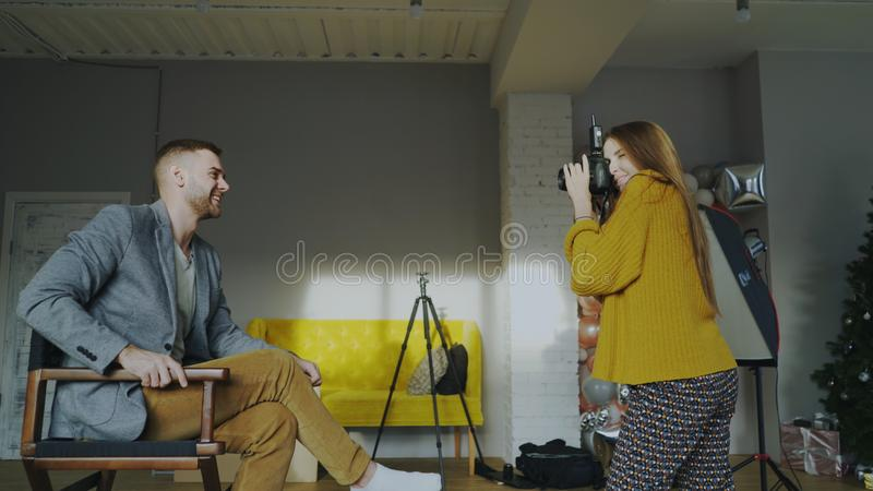 Professional photographer woman taking photo of businessman model girl with digital camera in studio. Professional photographer women taking photo of businessman royalty free stock photography