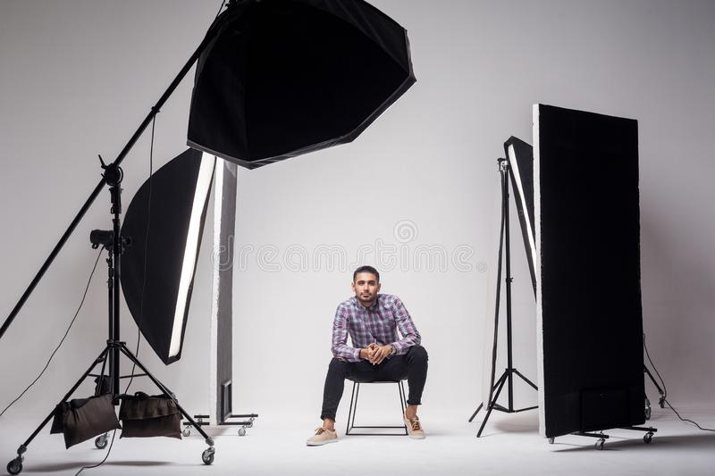Professional photography studio showing behind the scenes lights. fashion handsome young man model at studio in the light flashes. Sitting and looking at stock images