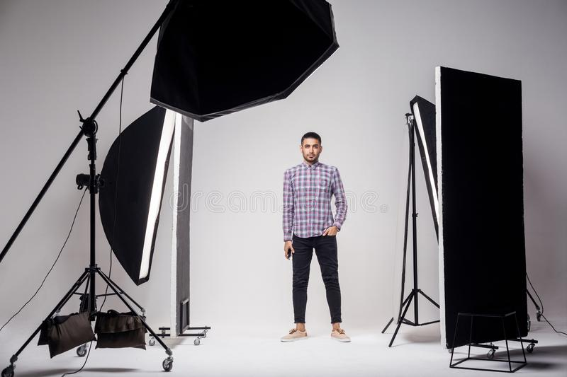 Professional photography studio showing behind the scenes lights. fashion handsome young man model at studio in the light flashes. Standing and looking at stock image
