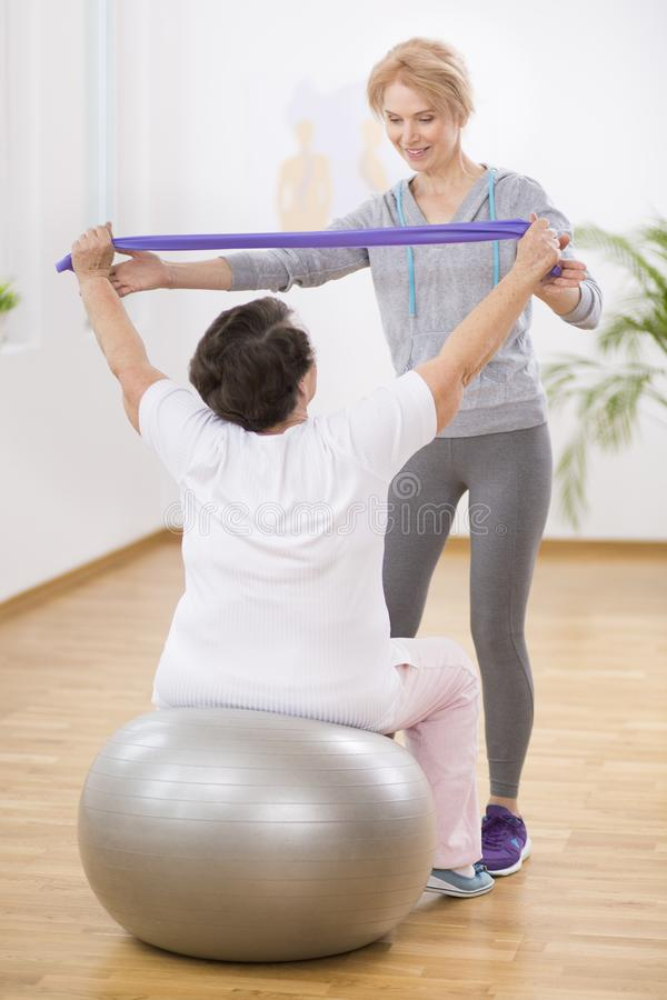 Professional physiotherapist helping senior woman sitting on the exercising ball with stretching tapes. Professional physiotherapist helping senior women sitting royalty free stock photos