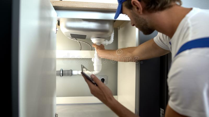 Professional plumber checking water pipes in kitchen, typing report in tablet stock photography