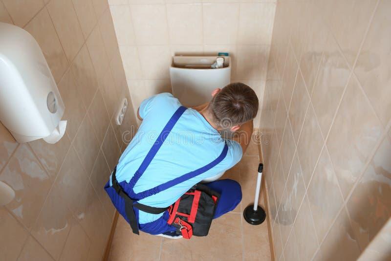 Professional plumber in uniform repairing toilet tank stock images
