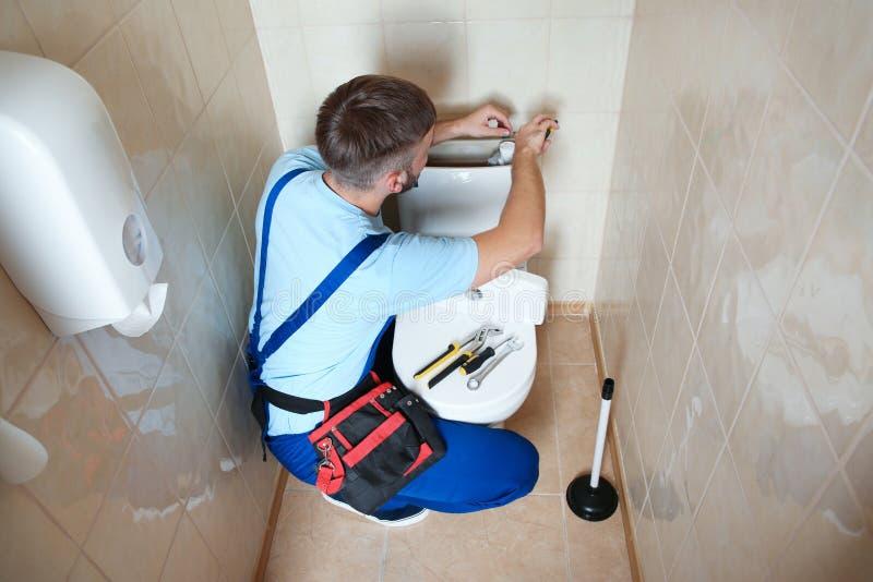 Professional plumber in uniform repairing toilet tank stock photo