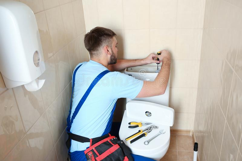 Professional plumber in uniform repairing toilet tank royalty free stock photography