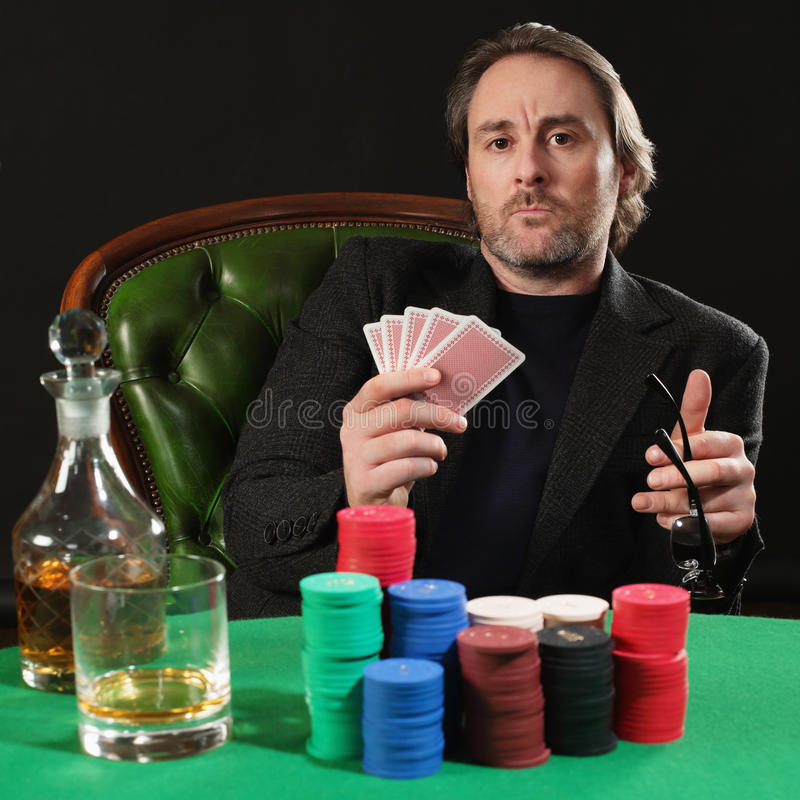 Professional poker player. Photo of a professional poker player with a large stack of gambling chips. Playing cards have been altered to be generic stock photos