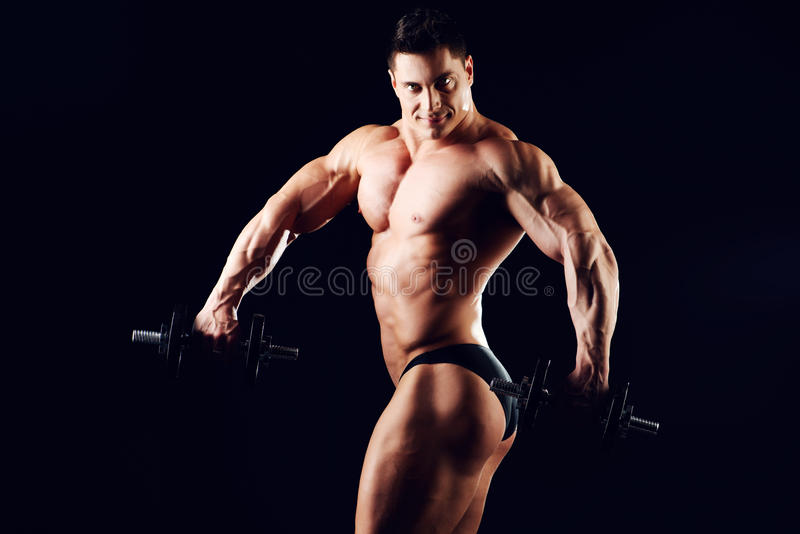 Professional. Portrait of a handsome muscular bodybuilder posing with dumbbells over black background stock image